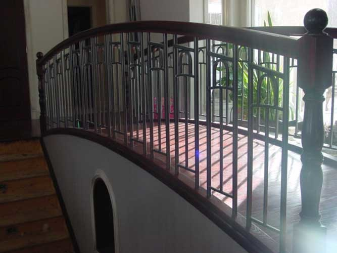 arched iron railing with wood banister