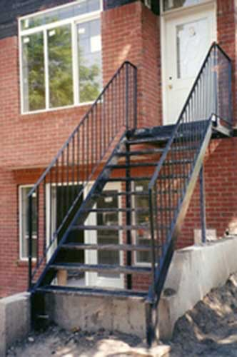 long metal staircase & railing on brick house