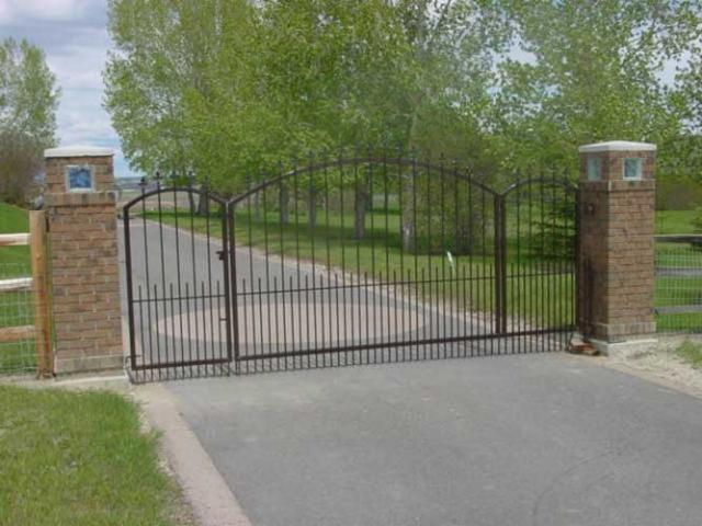 brown metal property gate on driveway