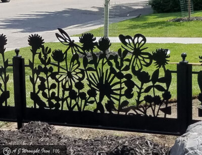 closeup of laser cut metal garden fence with flower pattern