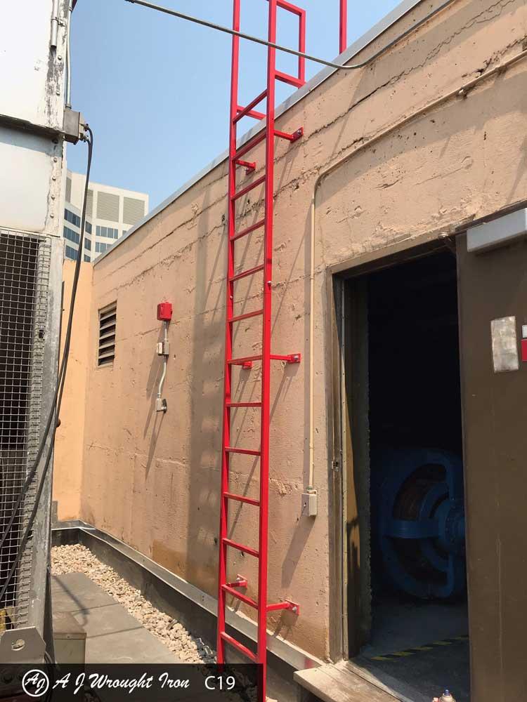 custom red metal ladder on side of building
