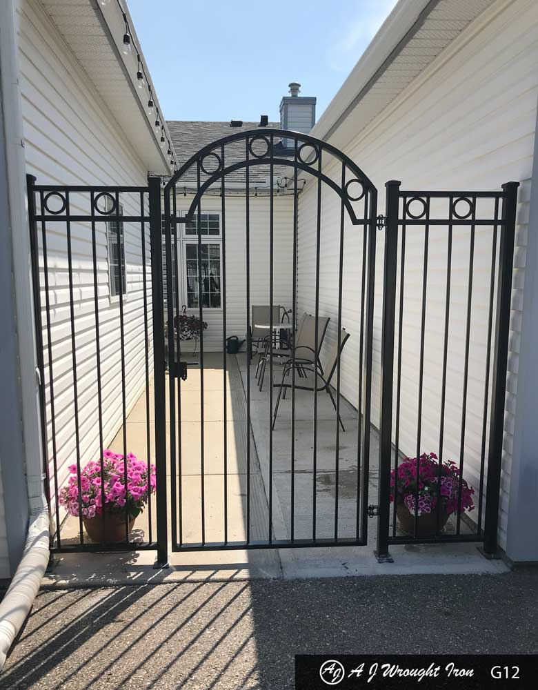 tall wrought iron garden gate on small patio